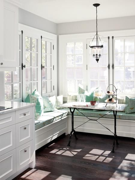 #white & pale #turquoise corner banquette with a French-style wrought iron footed marble topped kitchen table. old-style windows with wrought-iron cremones