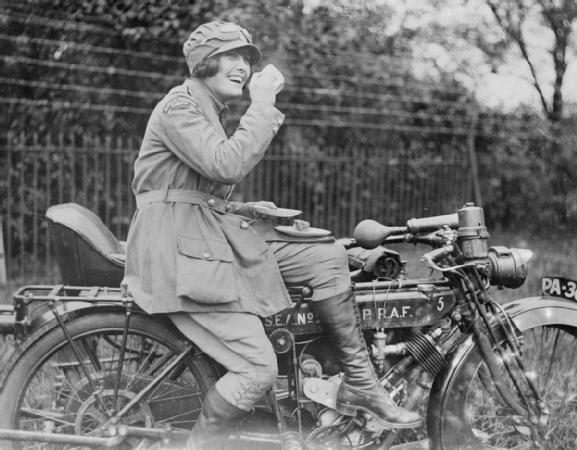 A dispatch rider in the Women's Royal Air Force (WRAF) enjoying a tea break while seated on her Phelon & Moore 500cc single cylinder motorcycle circa 1918.