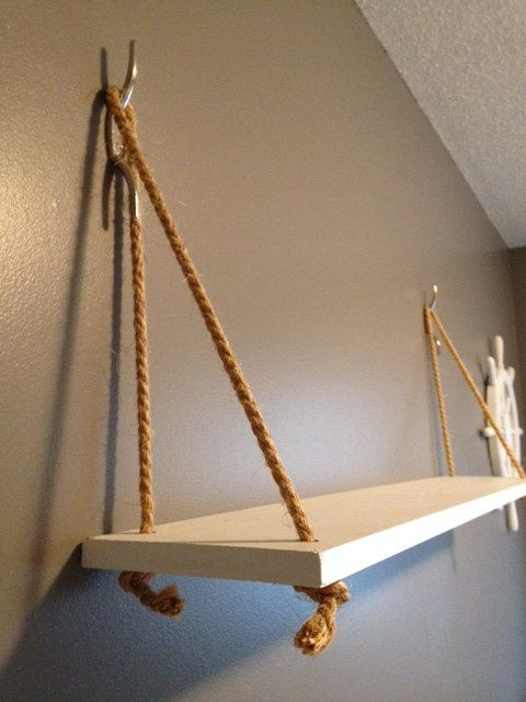 This is a nautical-themed hanging shelf made with painted wood and nautical rope. This is identical to a shelf sold by an upscale home decor