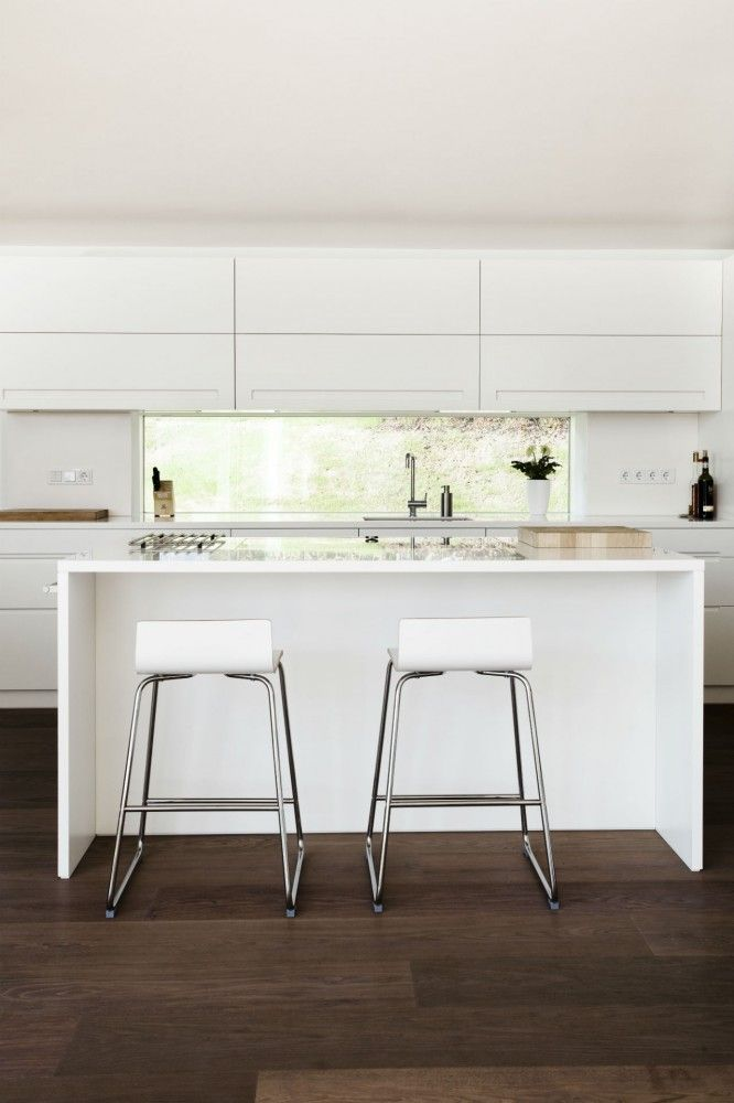 white kitchen, modern, bar stools tucked under kitchen island, timber flooring, open space.