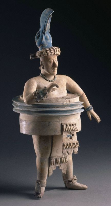 Ballplayer. Late Classic Maya, A.D. 600–800. Place made: Jaina Island or vicinity, Maya area, Campeche, Mexico. h. 34.2 cm., w. 17.8 cm. The massive padding around the waist of this figure identifies him as a ballplayer. Such protection was probably made out of long cloth wrappings, atop which was attached a ribbed, wooden striking element, painted blue on this example. His bird headdress may have been particular to his team. -Princeton University Art Museum-