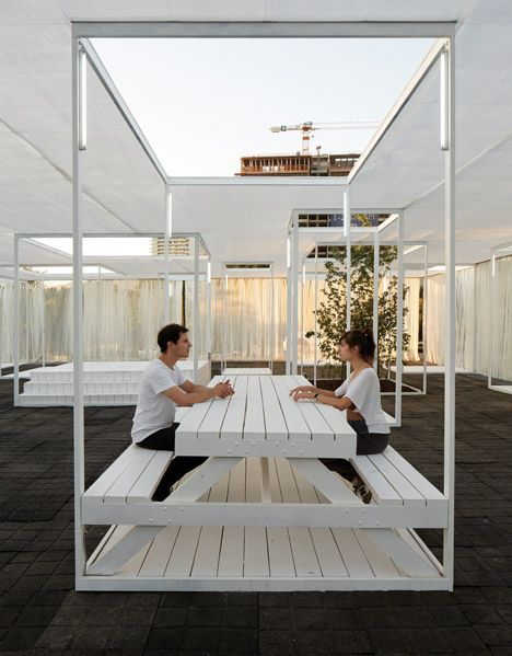 Trees and exhibition stands line up with skylights inside Umwelt's Ambient 30_60 pavilion