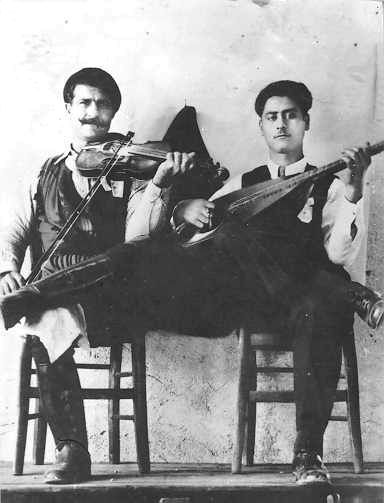 Cretan musicians. Koutzourelis [a well-known laouto player] and Mavros [a violin player]