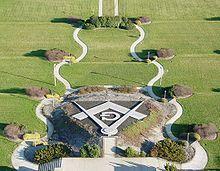 Photo en couleur d'un jardin avec monuments formant des symboles maçonniques