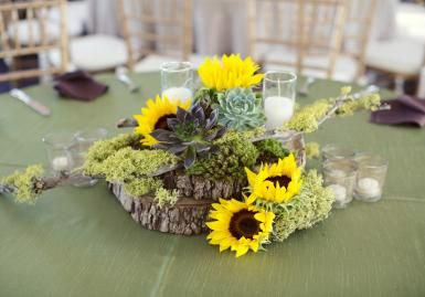 The slice of tree trunk with succulents and sunflowers makes the perfect centerpiece