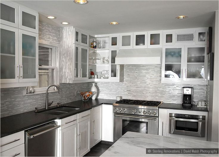 black countertop brown backsplash white cabinet black