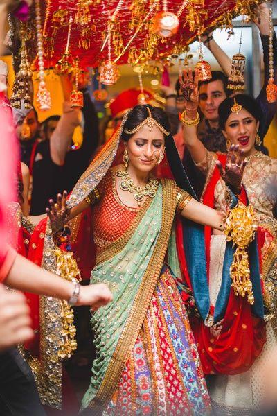Indian Wedding Photography - Dancing Entry of Bride wearing a Sabyasachi Paneled Lehenga with a Mint Green Dupatta | WedMeGood #wedmegood #indianbride #bridalentry #indianwedding #lehengas #dancing