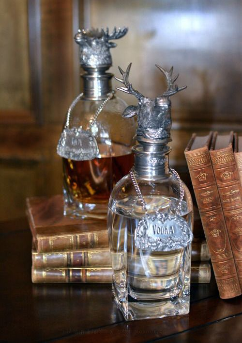 Decanters with stag stoppers and vintage leather books. http://annabelchaffer.com/