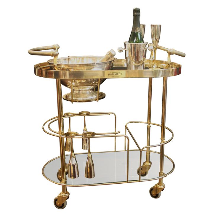 Art Deco Champagne Bar Cart by Pommery  France  20th c.  An Art Deco champagne trolley or rolling bar cart featuring a two-tiered curved frame of chromed brass and glass, the top tier with fitted silver bowl or wine cooler for ice, the second tier with six champagne flutes of silver and brass and Art Deco ice bucket, on vintage large casters.