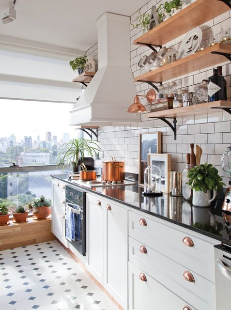 Cocina moderna en clave Nueva York: azulejos en blanco y juntas negras, piso en mosaico blanco y negro, artefactos en cobre, cuadros en la mesada y mucho sol. Foto: Magalí Saberian