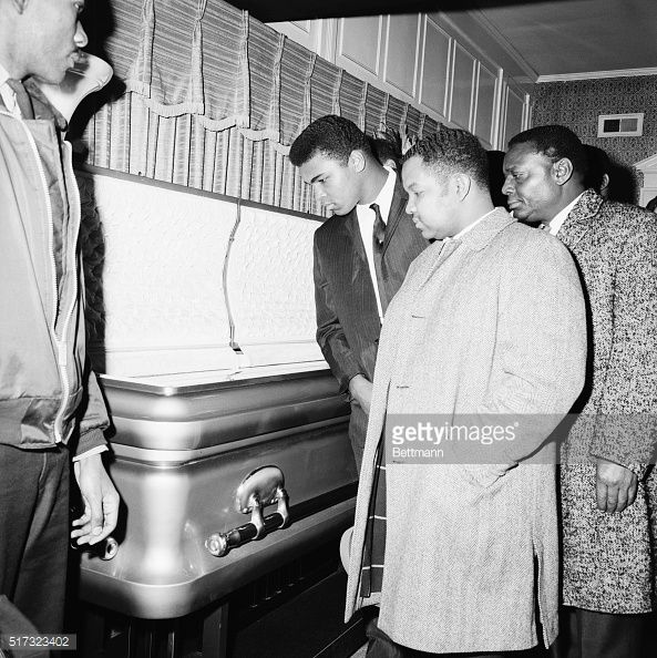 Heavyweight boxing champion Cassius Clay views the body of soul singer Sam Cooke at his wake in Chicago.