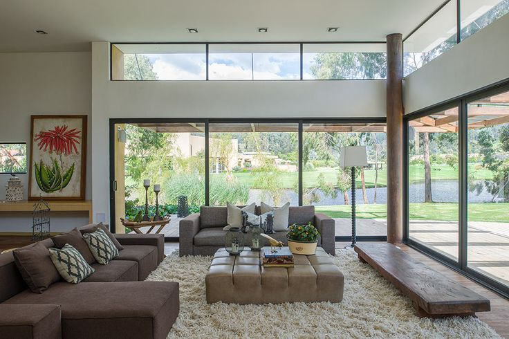 Sala, la vista lo es todo. A través del gran ventanal, la sala está relacionada íntimamente con el jardín y el lago. El amueblamiento con lino, cuero, fibras de lana y madera rústica resalta el carácter campestre de la casa.