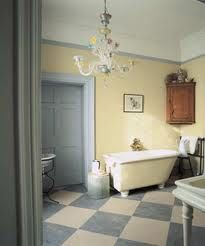 Diamond chequered floor, cream grey decor, chandelier, antique corner cupboard, roll top freestanding bath