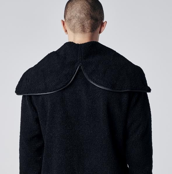 Faux shearling pullover hoodie with kangaroo pocket and Stampd embroidery at chest. Zippered split hood with elongated fabric pulls.