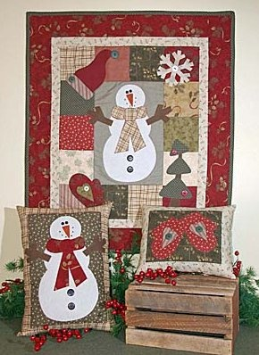 """Snow Day (Pattern)- 24"""" x 28"""" Wallhanging and Pillows. This Snowman takes center stage around a border of patched blocks. Cute & easy appliques decorate the background."""