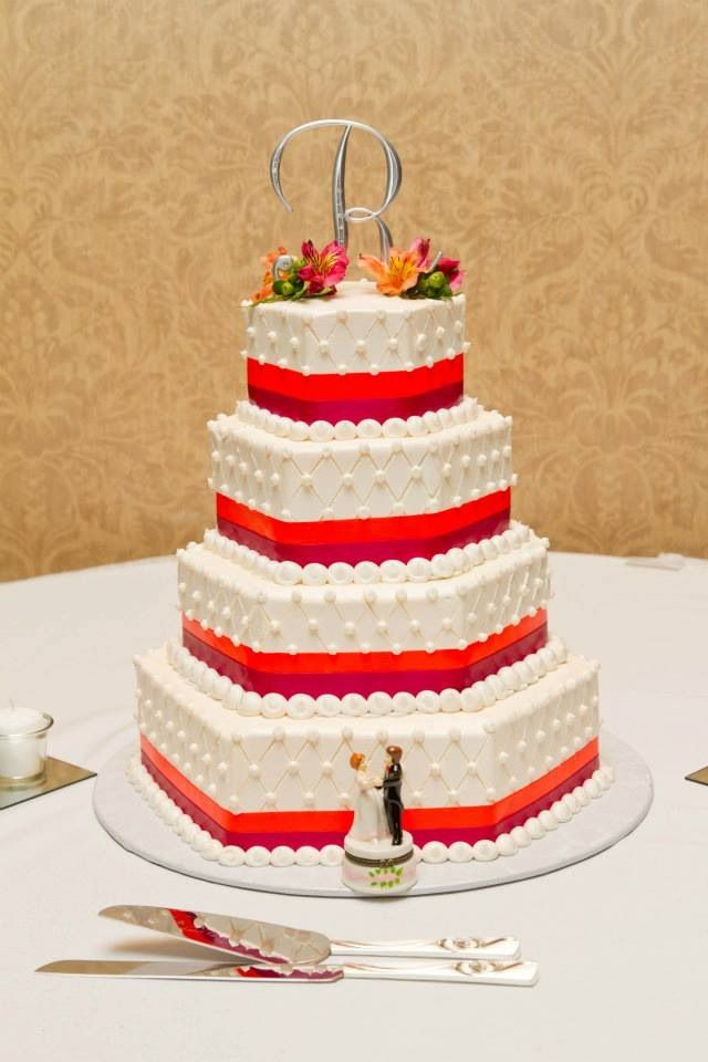 Hexagon wedding cake with pink and orange ribbon and ivory icing
