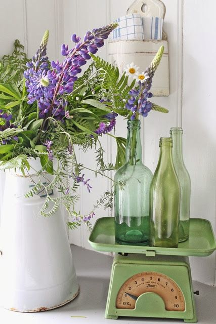 VIBEKE DESIGN:  green bottles displayed with an enamel pot of purple flowers.