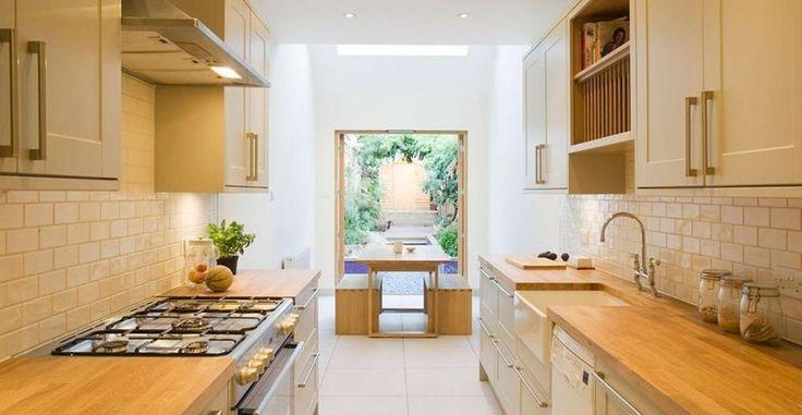 Come ristrutturare e ampliare una palazzina per due a Londra. Cucina e sala da pranzo comunicanti per 'Slim House': pavimento in grès porcellanato bianco e mobili su misura. la vetrata sul verde crea un effetto visivo riposante.