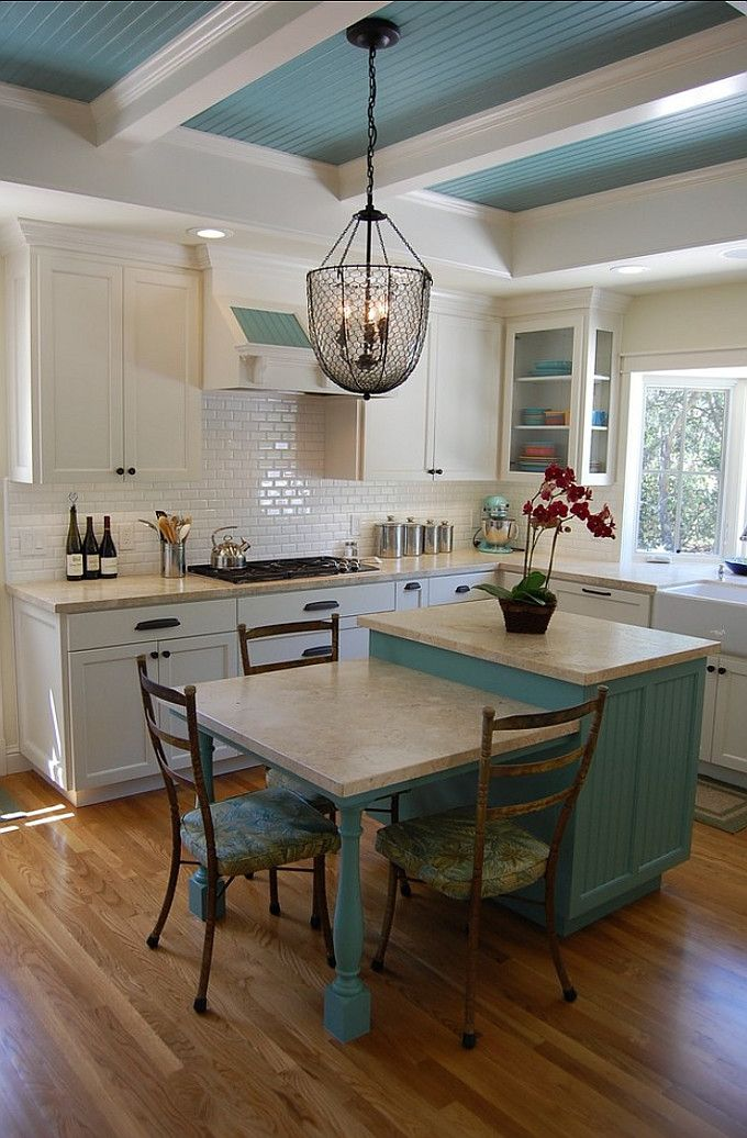 Love the painted beadboard ceiling and chicken wire light fixture. Clever island with seating, sub tiles and farm sink. Designed by R.A.D. Design-Build.