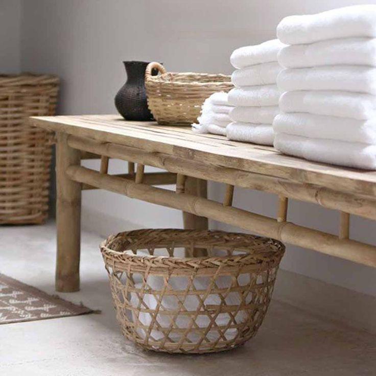 Panca da bagno in legno chiaro con appoggiati asciugamani bianchi e cesto