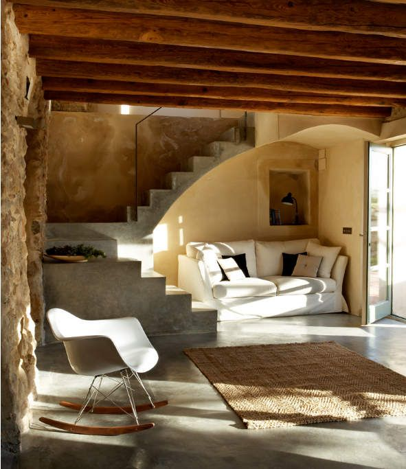 I am not sure that this is cob, but it would be a lovely design for a cob house.  Those are probably concrete steps.  I love the under the stairs couch nook.