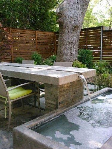 Déco de rêve sur une terrasse zen avec une table de jardin traversée par un circuit d'eau s'écoulant dans le bassin proche pour mieux y revenir grâce à une installation d'eau en circuit fermé.
