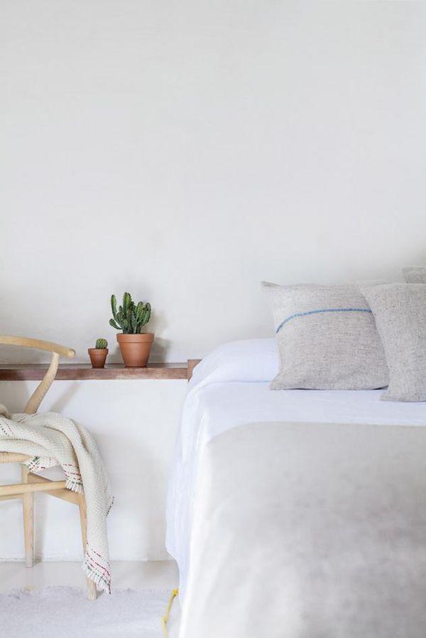 une chambre avec une atmosphère douce et minimaliste, décorée simplement avec quelques cactus et une chaise en bois
