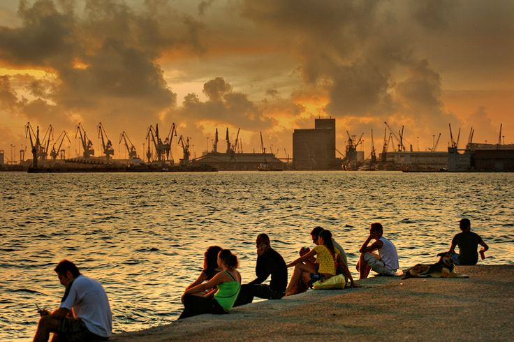 people enjoying the sun set at the seafront of Thessaloniki.