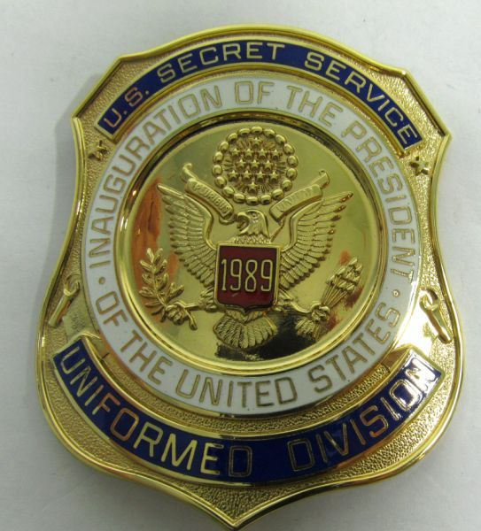 "Lot 37 in the 9.3.13 online & live Auction! 1989 Presidential Inauguration United States Secret Service / Uniformed Division badge, a great find for any collector of political Americana. Reads ""U.S. Secret Service Division Inauguration of the President of the United States."" Includes engraving of U.S. seal. Bald Eagle w/ an olive branch & arrows in its talons, representing the original 13 colonies, and clutching a scroll with ""E Pluribus Unum"" meaning ""out of many, one"". #USA #POGAuctions"