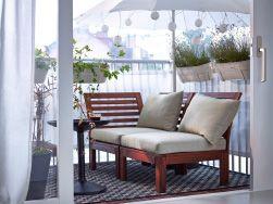 Balcone con sedie pieghevoli in legno marrone, tavolo a ribalta, panche/contenitori e supporti per piante in acciaio
