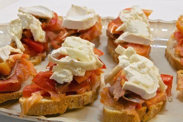 Canapés de salmón marinado con queso de cabra y anchoas. Un aperitivo muy potente con sabores fuertes como las anchoas y el queso de cabra, acompañado de jugoso salmón marinado y tomate, sobre una tostada crujiente. Una delicia!