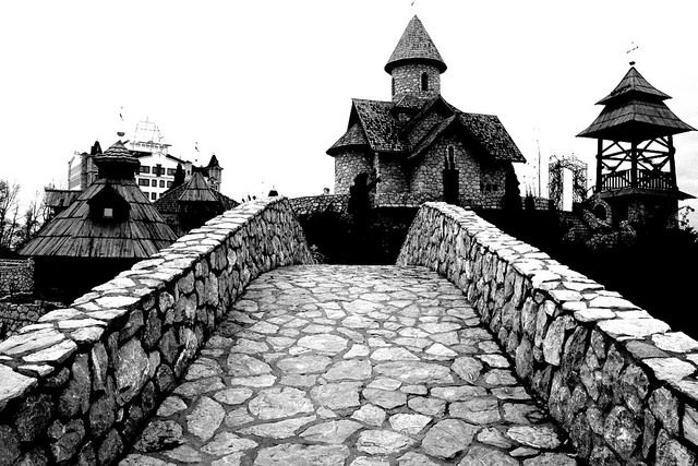 Old stone structures are part of traditional Serbian architecture. This is an example of the beautiful structures of old, in the Ethno Village of Stanisici, in the Republic of Serbia. In the background is the beautiful Churich of Sveti Nikola, or St. Nicholas.