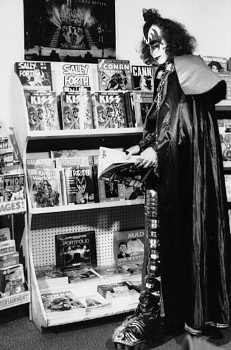 Gene Simmons reads.    Gene Simmons checking on the merchandise.