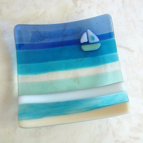 A charming beach fused glass plate with relaxing Aquamarine Blue, White swirls, Turquoise and clear water and waves, Vanilla beach, Blue skies, and a little Mint, White, and Aqua sailing boat... This plate has an additional layer of clear glass on the back for a more elegant look and
