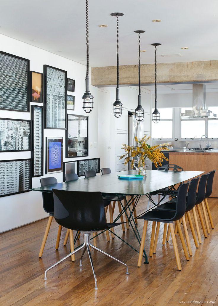 Sala de jantar tem mesa e cadeiras pretas, luminárias com estilo industrial e parede galeria.