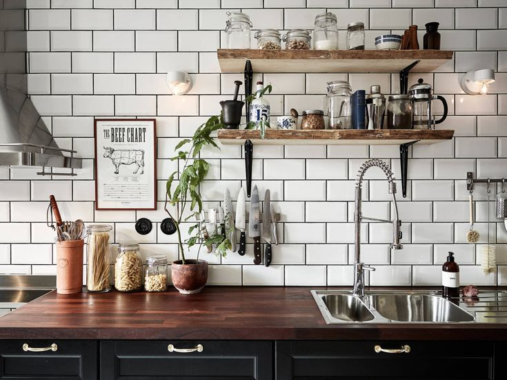 Black kitchen with subway tiles and open shelves