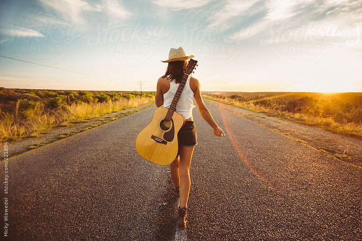 Female musician with a guitar hitchhiking on an open country road by Micky Wiswedel