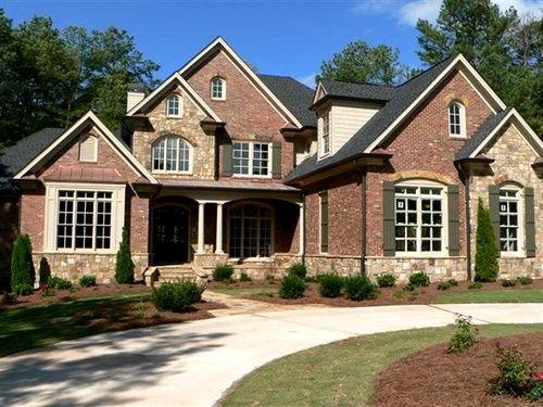 A circular drive leads up to this brick and stone home, which has a three-car garage. Love it!