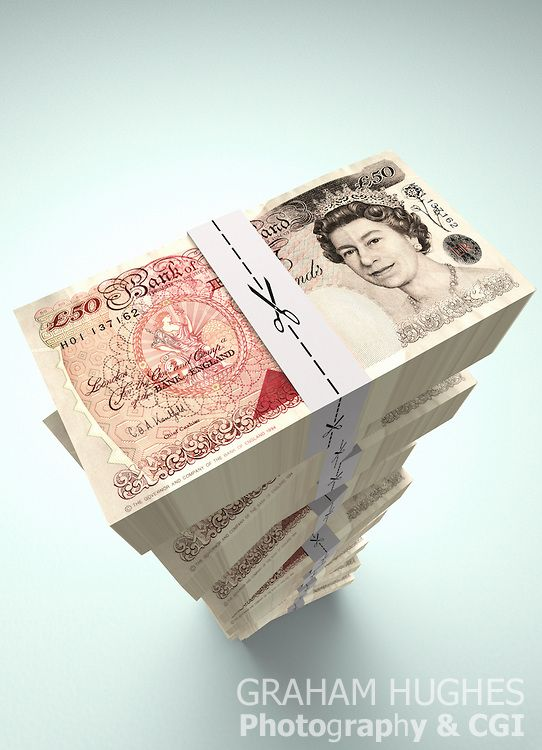 Stack of £50 pound British bank notes with scissors cutting along dotted line on money ties.