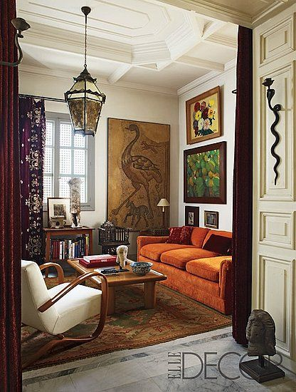 Artist Nabil Nahas' eclectic apartment - I love the orange couch, cream walls and gallery art display. 16' ceilings wouldn't suck either