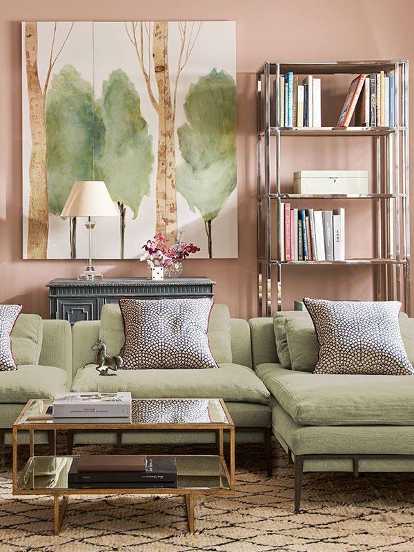 Everything about this informal sitting room is calming - from the gentle colour palette of pale green and pink, to the wall art featuring a sparse forest, to the deep woollen rug with its clean pattern.