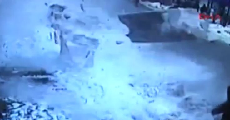 CCTV captures the moment an insane amount of snow wipes out people in the street after snow slips from the roof of a mosque