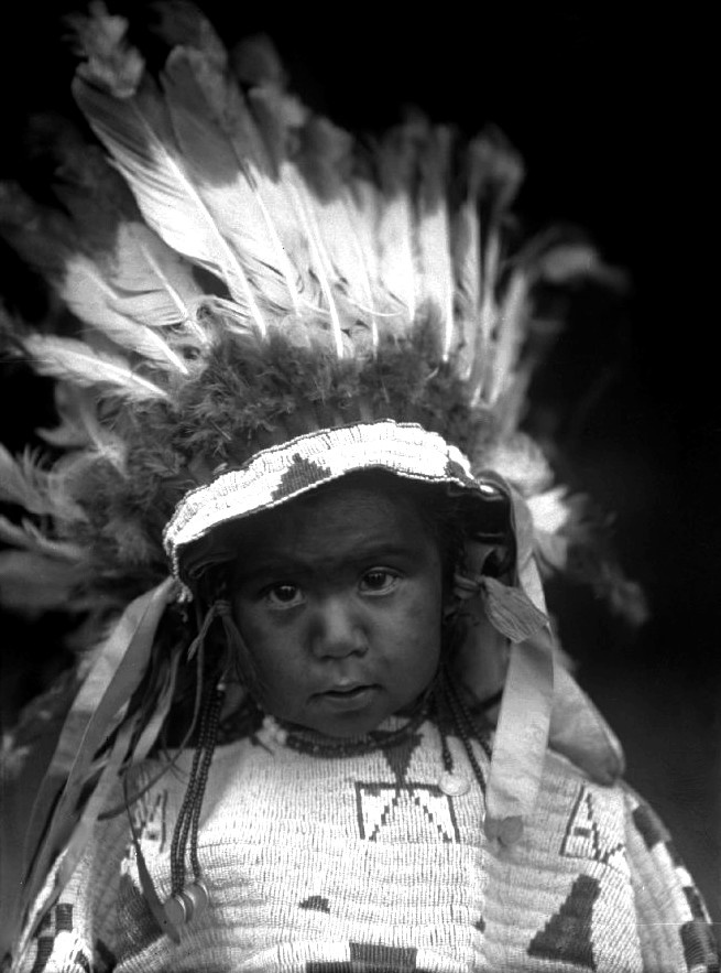 Sioux boy, Little Bear Comes Out; he wears a feather headdress and beaded hide shirt. Photo: 1909.