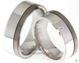 Strak van vormgeving, zijn deze trouwringen van 7 mm. breed. De ringen bestaan uit een brede, glanzende baan van witgoud en een smallere baan van titanium.  De dames trouwring is bezet met een  prinses geslepen diamant van 0,08 crt.