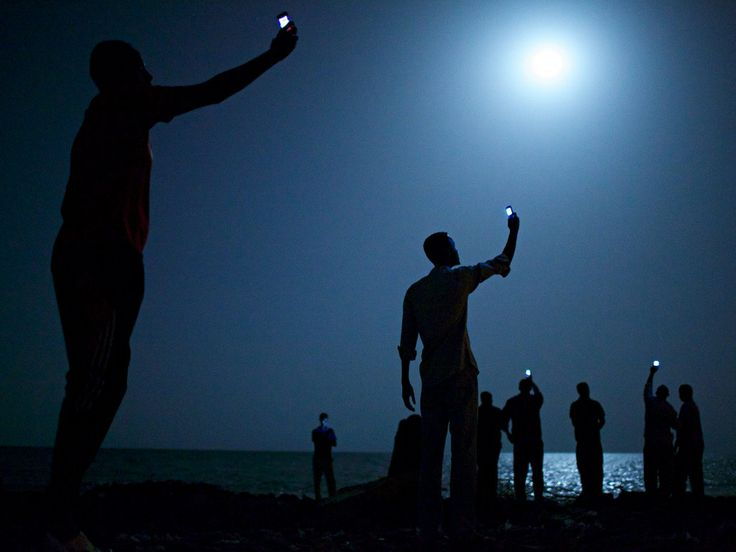 Signal by John Stanmeyer is the World Press Photo of the Year 2013 --- African migrants on the shore of Djibouti at night, raising their phones in an attempt to capture an inexpensive signal from neighbouring Somalia.