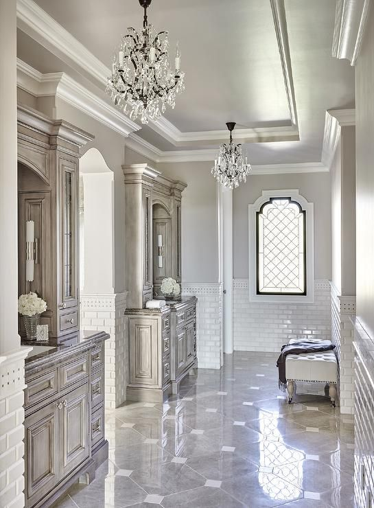Luxurious long gray French master bathroom is clad in gray marble diamond  pattern floor tiles with square inlays of white marble accented by white