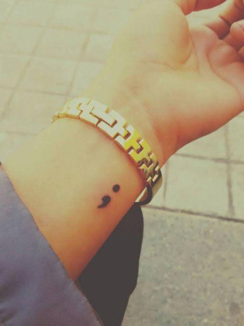 Tatuaje del punto y la coma en el interior de la muñeca...