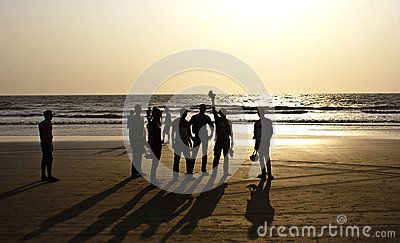 A group of friends silhouetted at Arambol Beach, North Goa, with Sun setting at the backdrop.