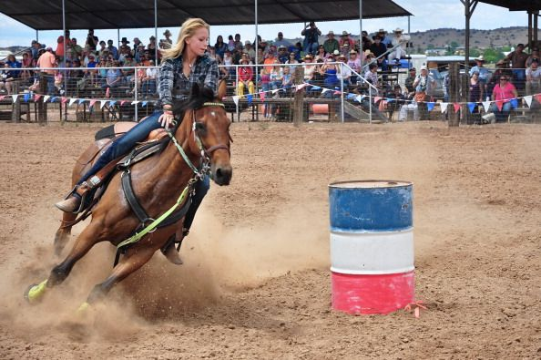 A rodeo cowgirl and her horse negotiate a barrel during the barrel racing competition at the annual Rodeo de Galisteo in Galisteo a small town in...