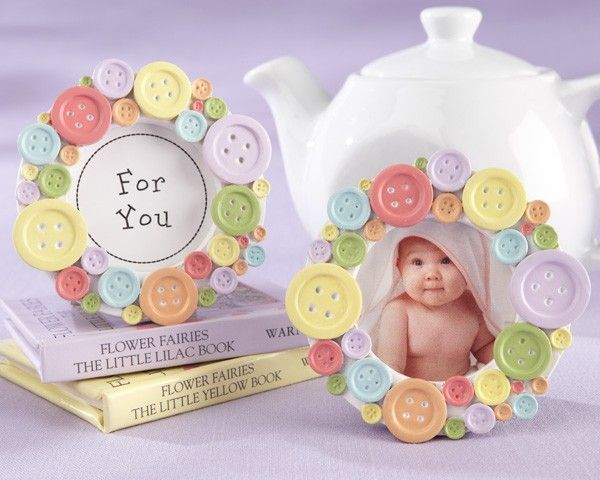 "Mom always says, ""Button up to stay warm and cozy!"" We have a rainbow of buttons cozying up to create this adorable photo frame favor so full of warmth for baby showers! The funny thing is, our fantastic ""Cute as a Button"" photo frame makes thanking your shower guests a snap!Multi-colored, resin buttons in various sizes on a circular, white base with a gray frame stand on the back Center insert says ""For You"" Frame measures approximately 3"" in diameter Coordinates with the ""Cute as a…"